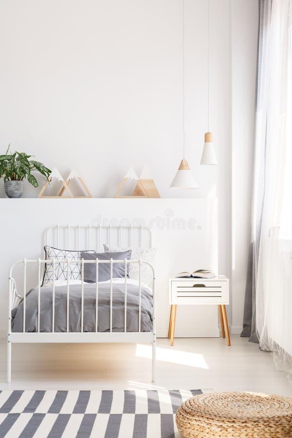 Poef op gevormd tapijt dichtbij grijs bed in witte jong geitje` s slaapkamer binnen stock foto's