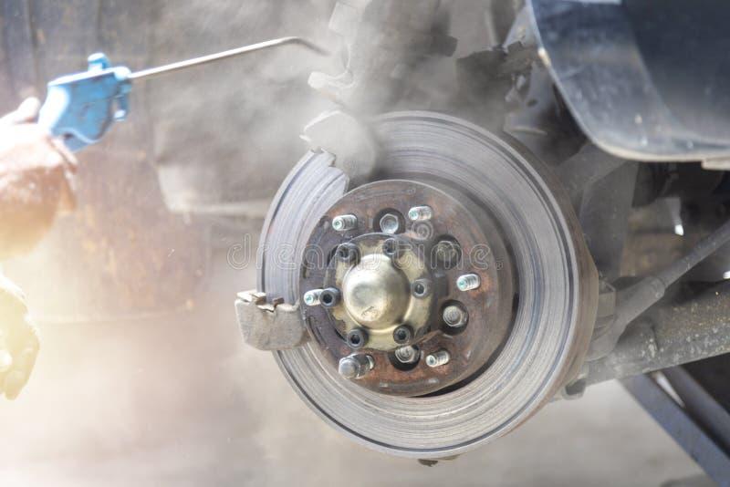 A poeira limpa da tomada da ruptura do disco da pistola pneumática do uso do mecânico remove antes da pancadinha da ruptura da mu fotografia de stock royalty free