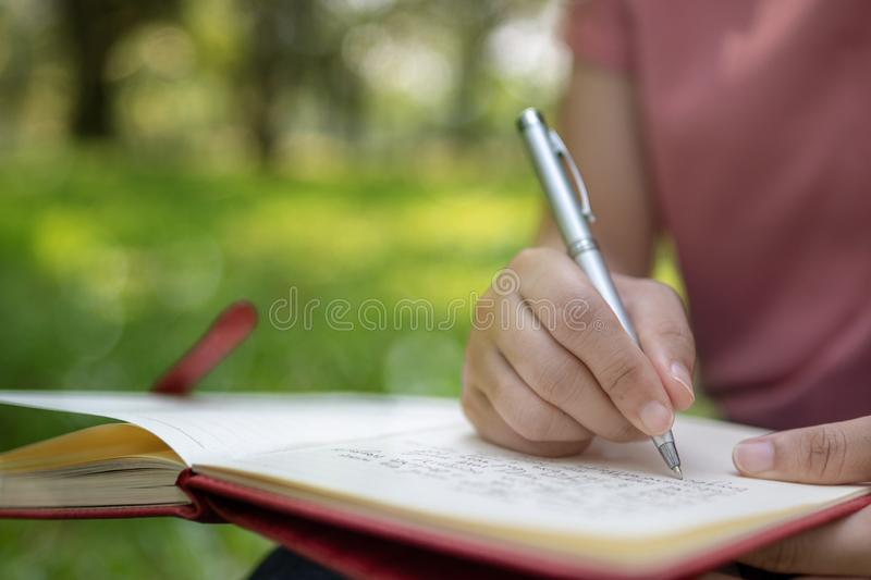 poem, poetry and knowledge education concept,  close up sitting writing on notebook in park stock images