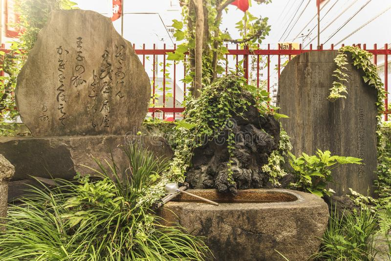 Poem of the 18th century Japanese poet Ota Nanpo on a large stone in the Shintoist Shozoku Inari Shrine. Poem of the 18th century Japanese poet Ota Nanpo on a stock images