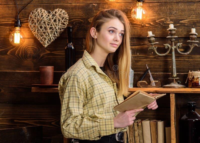 Poesieabendkonzept Mädchenlesepoesie in der warmen Atmosphäre Dame auf träumerischem Gesicht in der Plaidkleidung hält das Buch u lizenzfreies stockbild