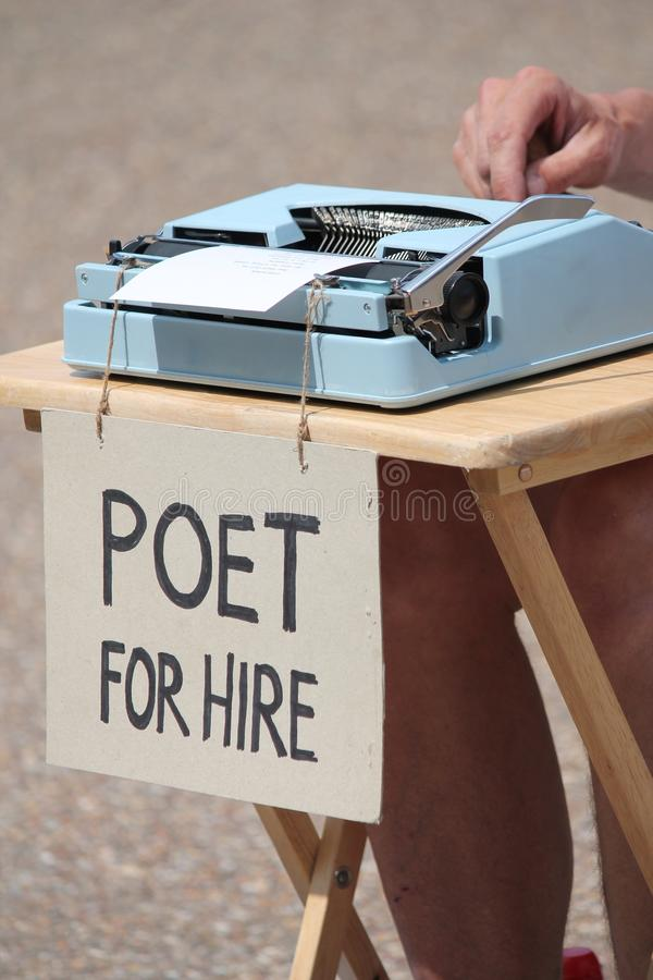 Poet for hire with typewriter. And sign stock image