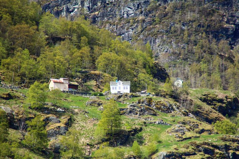 Poetic scenery of white house at the middle of mountain with steep cliff. In Norway royalty free stock photo