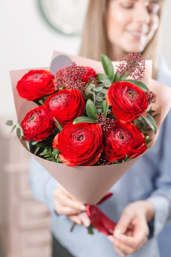 pogodna ranek wiosna Młoda szczęśliwa kobieta trzyma piękną wiązkę czerwoni jaskiery lub Ranunculus w ona ręki prezent zdjęcia royalty free