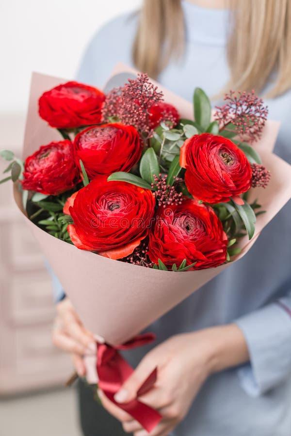 pogodna ranek wiosna Młoda szczęśliwa kobieta trzyma piękną wiązkę czerwoni jaskiery lub Ranunculus w ona ręki prezent zdjęcie royalty free