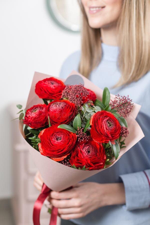 pogodna ranek wiosna Młoda szczęśliwa kobieta trzyma piękną wiązkę czerwoni jaskiery lub Ranunculus w ona ręki prezent zdjęcia stock