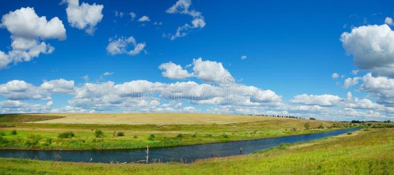 Pogodnego lata panoramiczny krajobraz z rzeką, złotymi polami, zielonymi wzgórzami i pięknymi chmurami w niebieskim niebie, obrazy stock