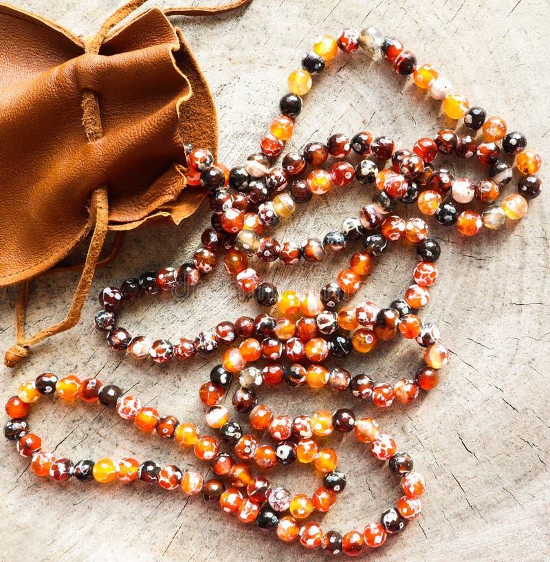 Pogodni koraliki złocista graba faceted agat z rzemienną biżuterii kieszonki torbą na nieociosanym tle zdjęcie royalty free