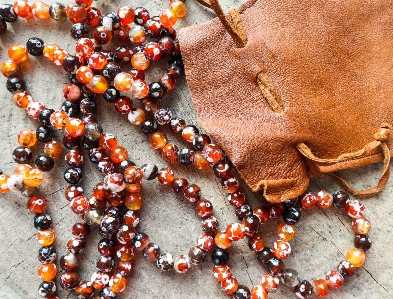 Pogodni koraliki złocista graba faceted agat z rzemienną biżuterii kieszonki torbą na nieociosanym tle fotografia stock