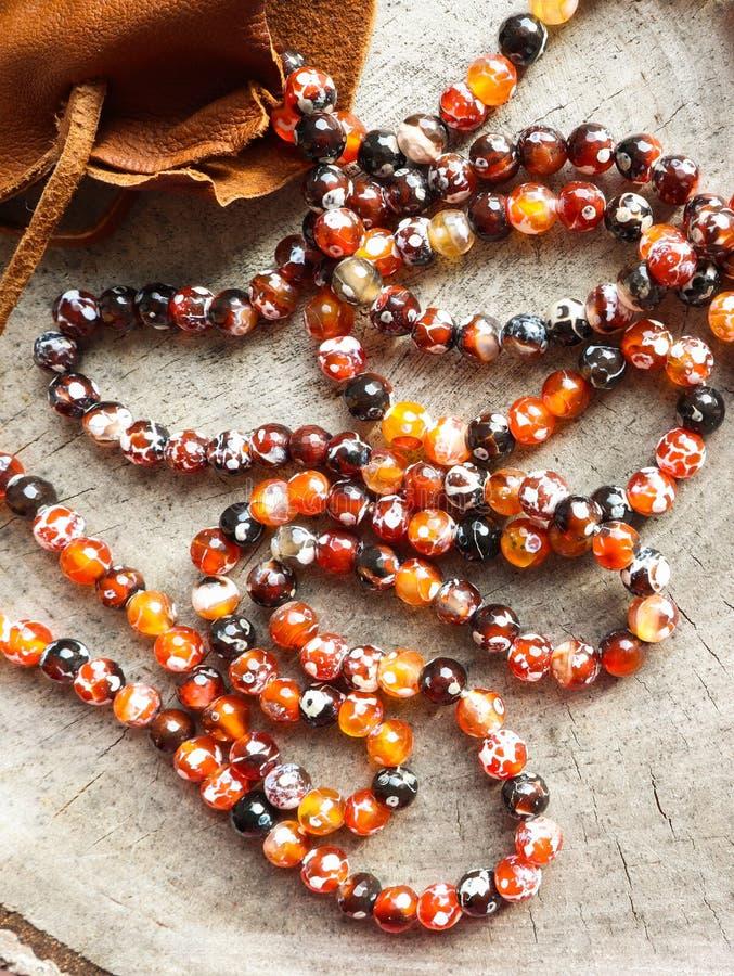 Pogodni koraliki złocista graba faceted agat z rzemienną biżuterii kieszonki torbą na nieociosanym tle obrazy royalty free