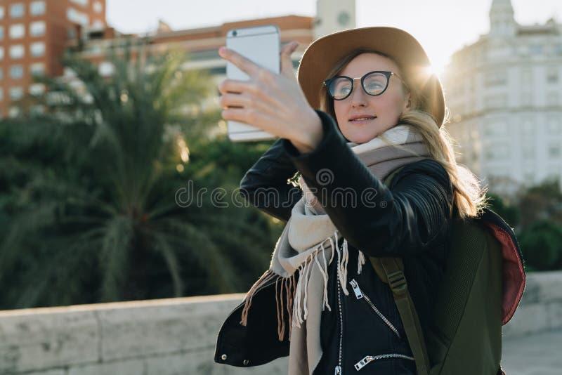 Pogodny jesień dzień, backlight Młoda atrakcyjna kobieta podróżuje w kapeluszu, eyeglasses, z plecaków stojakami na miasto ulicie zdjęcia stock