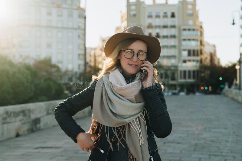 Pogodny jesień dzień, backlight Młoda atrakcyjna kobieta podróżuje w kapeluszu i eyeglasses stojakach na miasto ulicie fotografia royalty free