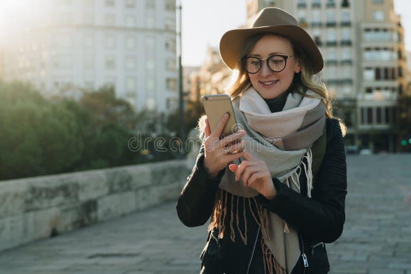 Pogodny jesień dzień, backlight Młoda atrakcyjna kobieta podróżuje w kapeluszu i eyeglasses stojaki na miasto ulicie, używają sma zdjęcia royalty free
