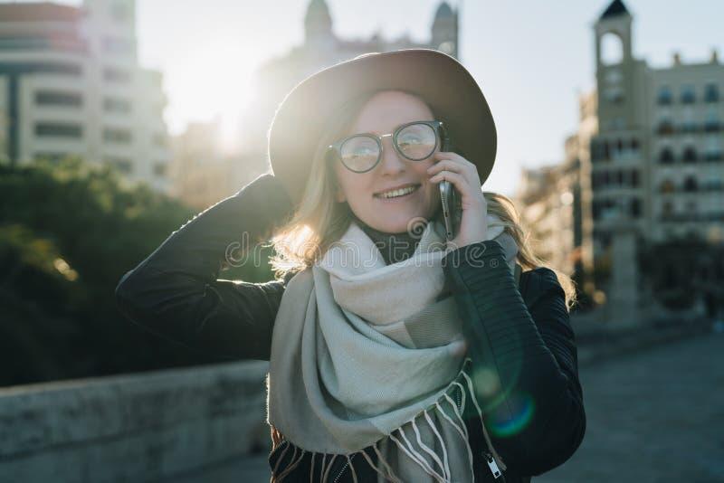 Pogodny jesień dzień, backlight Młody atrakcyjny kobieta turysta w kapeluszu i eyeglasses stojakach na miasto ulicie zdjęcie royalty free