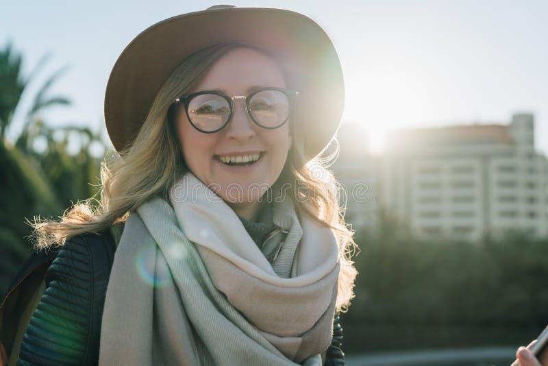 Pogodny jesień dzień, backlight Młody atrakcyjny kobieta turysta w kapeluszu z plecaków stojakami na miasto ulicie i, eyeglasses zdjęcie royalty free