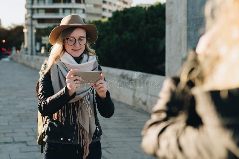 pogodny jesień dzień Młoda atrakcyjna kobieta podróżuje w kapeluszu i eyeglasses stojaki na miasto ulicie, używają smartphone zdjęcia royalty free