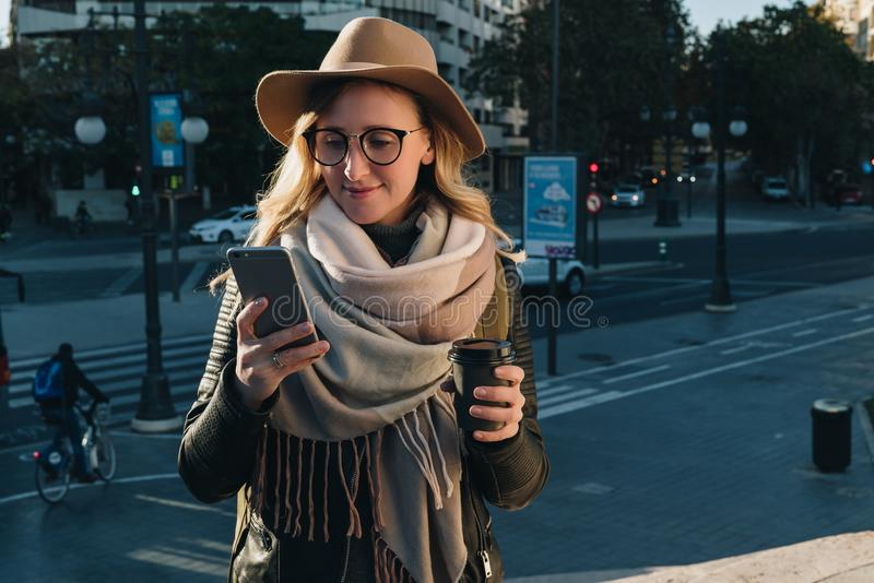 pogodny jesień dzień Młody atrakcyjny kobieta turysta w kapeluszu i eyeglasses stojakach na miasto ulicie, uses smartphone obrazy stock