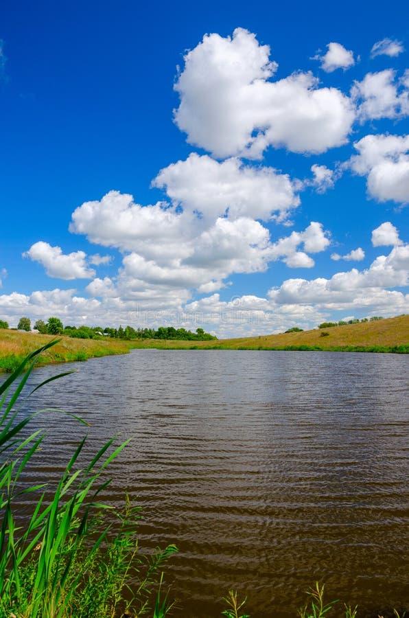 Pogodny lato krajobraz z rzeką, rolnymi polami, zielonymi wzgórzami i pięknymi chmurami w niebieskim niebie, obraz royalty free