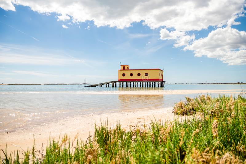 Pogodny plażowy widok dziejowy strażnika budynek w Fuseta, Ria Formosa Naturalny park, Portugalia fotografia royalty free