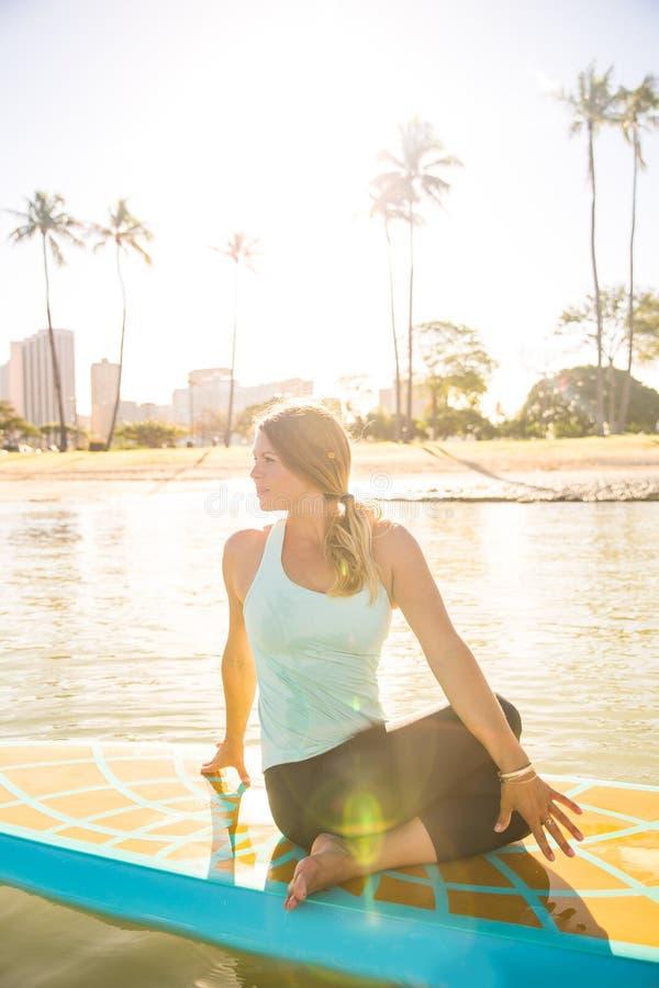 Pogodny ranku słońca racy moment ładna młoda kobieta w SUP Yo obrazy stock