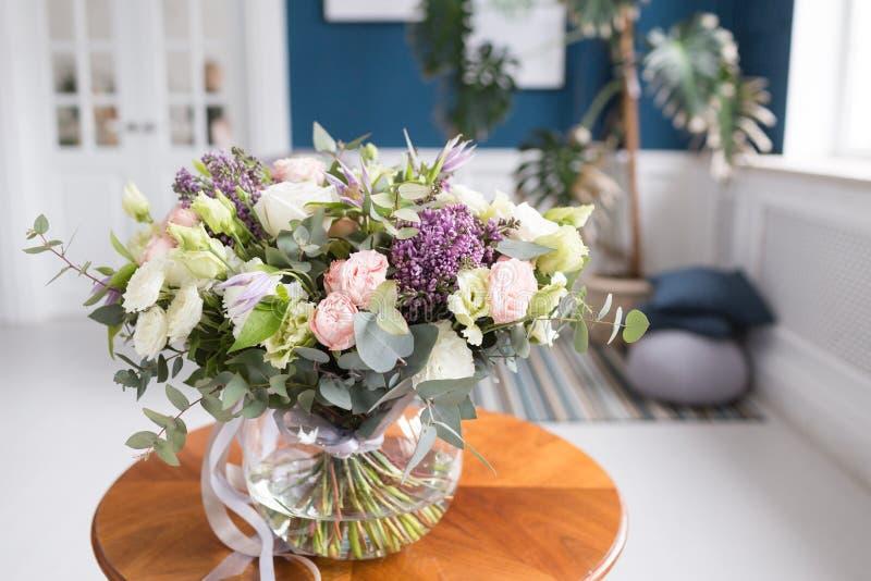 Pogodny wiosna ranek w żywym pokoju Piękny luksusowy bukiet mieszani kwiaty w szklanej wazie na drewnianym stole Praca zdjęcie royalty free