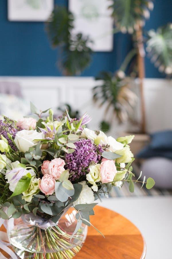 Pogodny wiosna ranek w żywym pokoju Piękny luksusowy bukiet mieszani kwiaty w szklanej wazie na drewnianym stole Praca zdjęcia royalty free