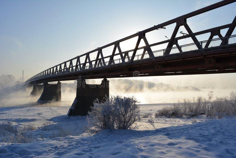 Pogodny zima dzień z mostem nad rzeką która no marznie, obraz stock