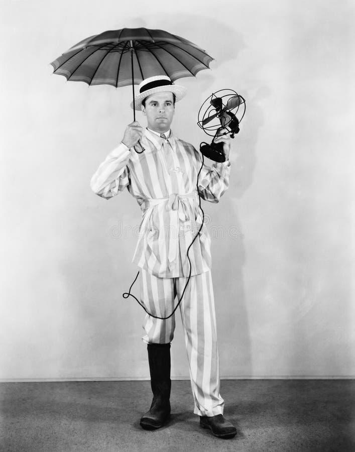 Pogodowy mężczyzna z parasolem, but i fan, (Wszystkie persons przedstawiający no są długiego utrzymania i żadny nieruchomość istn zdjęcia royalty free