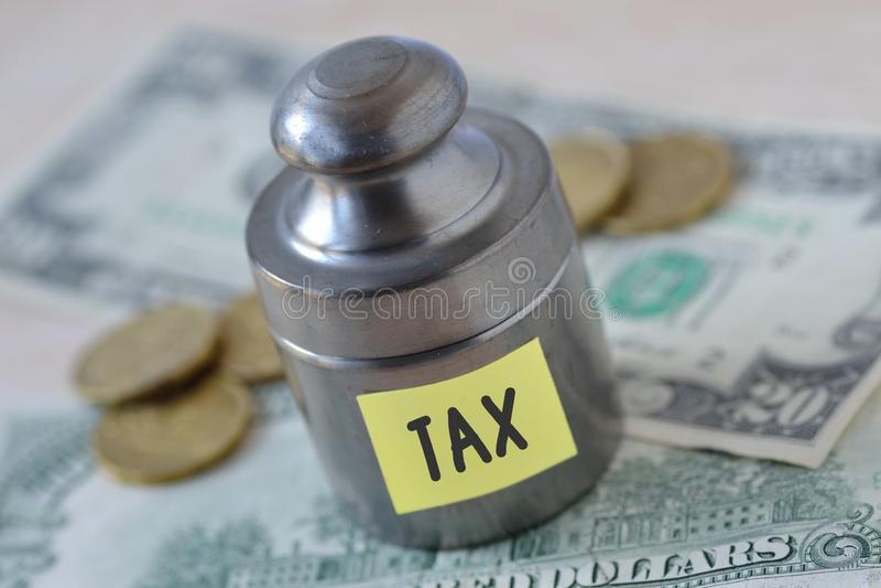 Poids avec l'impôt de mot écrit sur la note de papier sur le banknot du dollar image stock