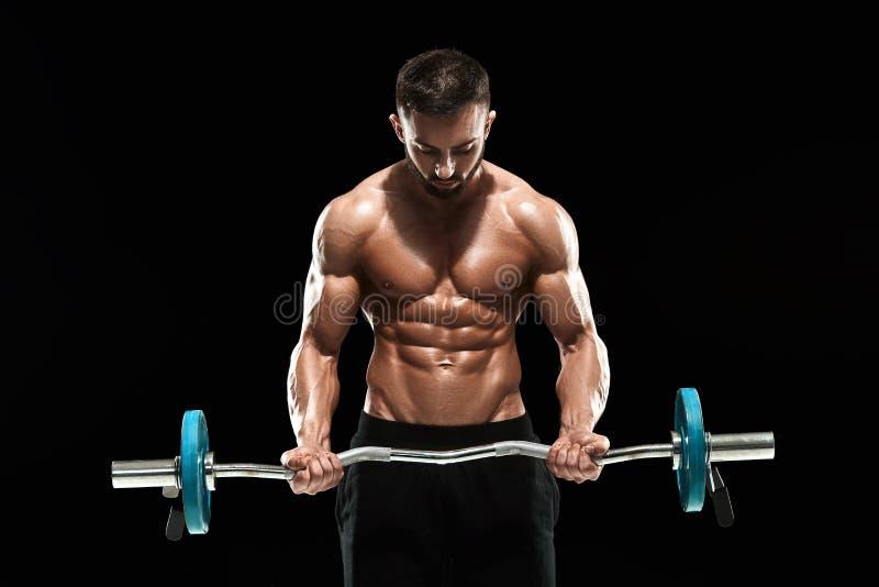 Poids de levage d'homme musculaire au-dessus de fond foncé photo libre de droits