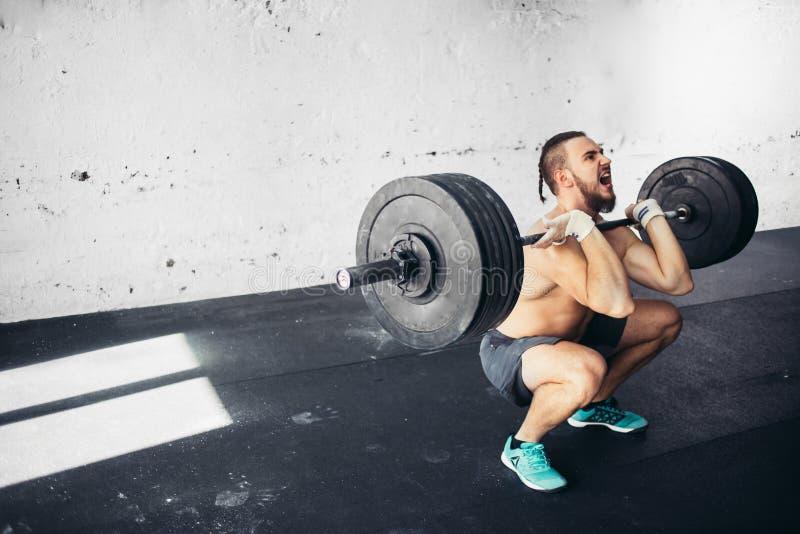 Poids de levage d'homme Séance d'entraînement musculaire d'homme dans le gymnase faisant des exercices avec le barbell photo stock