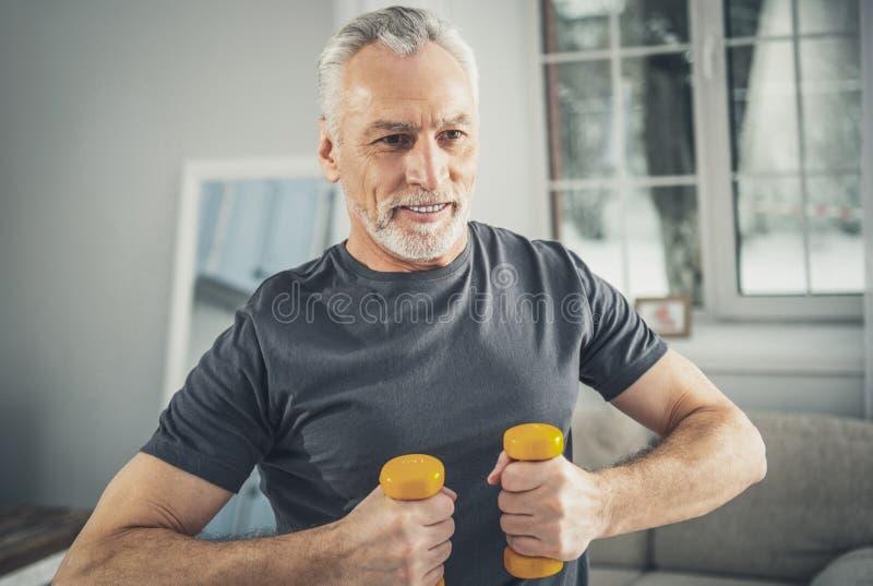 Poids de main de participation de sportif faisant des exercices de matin photo stock