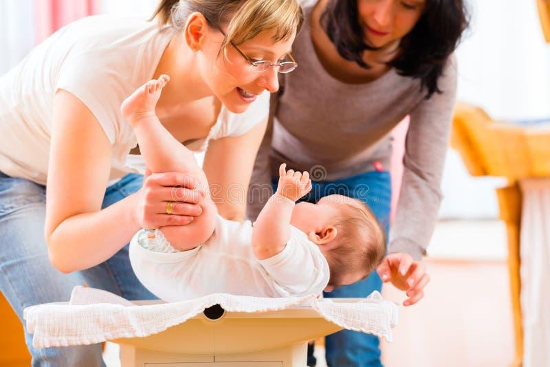 Poids de mesure de sage-femme ou bébé nouveau-né photographie stock