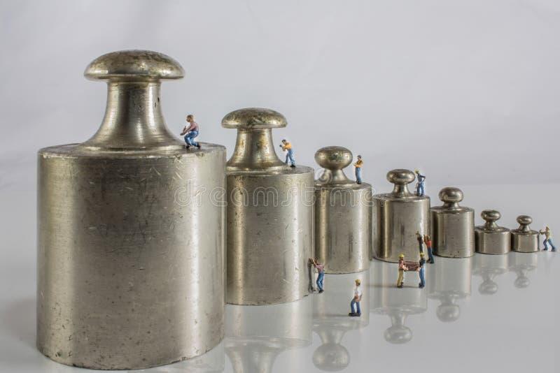 Poids pour l'équilibre avec les travailleurs miniatures images libres de droits