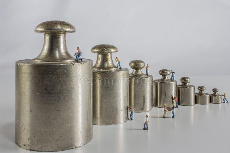 Poids pour l'équilibre avec les travailleurs miniatures photos stock