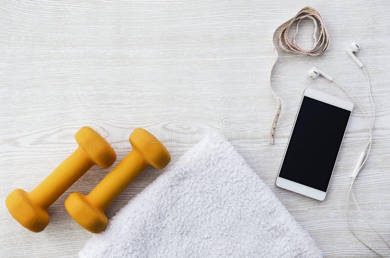 Poids, serviette, téléphone, écouteurs et bande oranges de mesure sur la table en bois blanche photo libre de droits