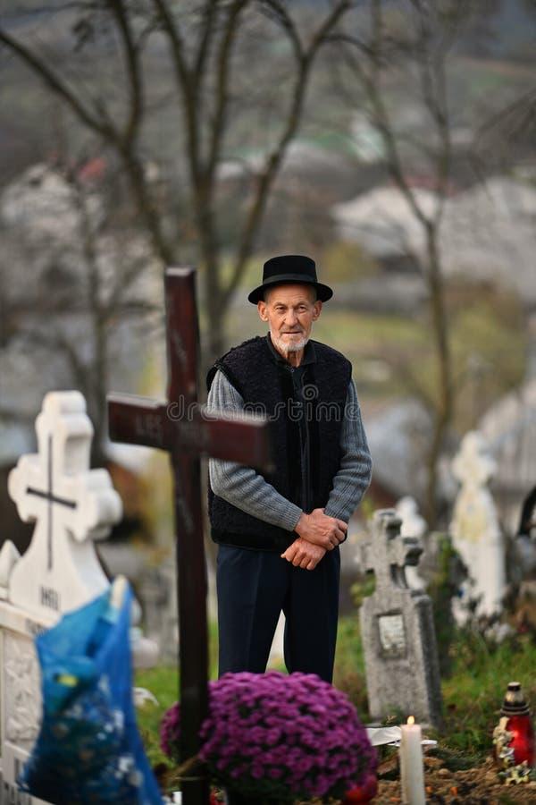 Poienile Izei, Maramures, Romania, il 19 ottobre 2018: Persona che prega nel cimitero al giorno santo immagine stock