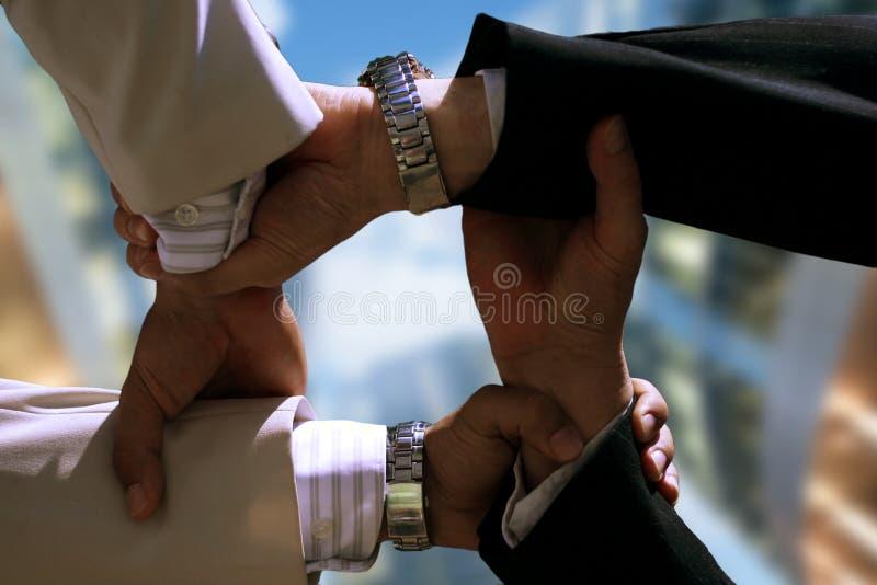 Poignée à quatre mains en gros plan des hommes d'affaires photos stock