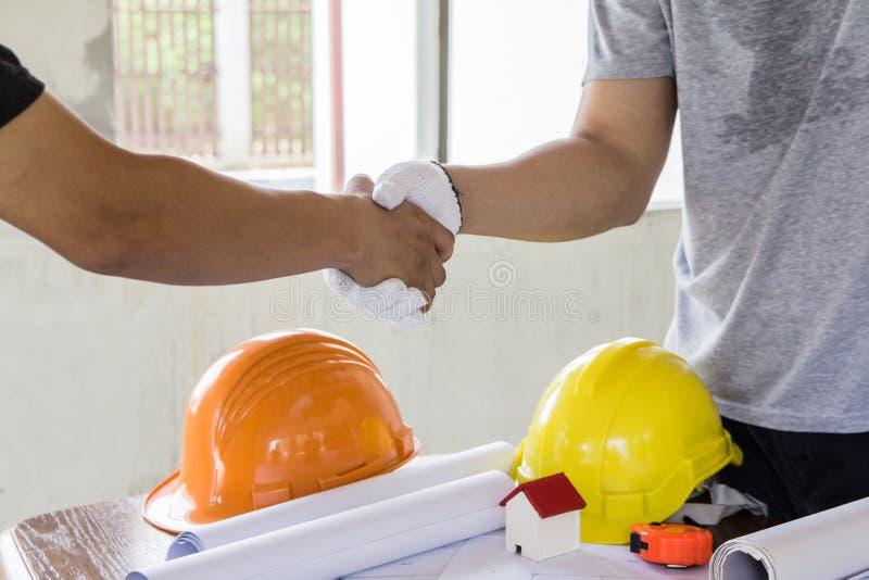 Poignée de main asiatique d'ingénieur pour le travail d'équipe dans la conception d'intérieurs et le plan de construction photos libres de droits