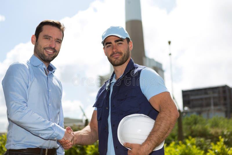 Poignée de main d'électricien et d'ingénieur devant le St électrique image stock