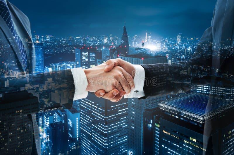 Poignée de main d'affaires avec la ville de scène de nuit photo stock