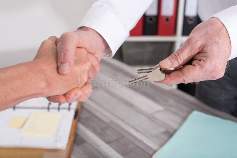 Poignée de main dans une transaction d'immobiliers images stock