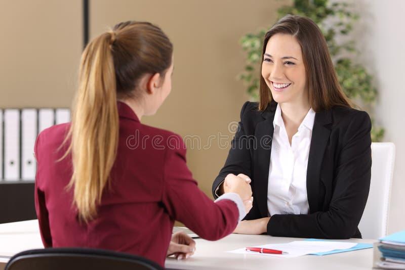 Poignée de main de deux femmes d'affaires au bureau photo stock