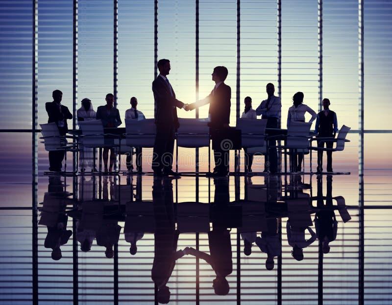 Poignée de main de deux hommes d'affaires avec leurs collègues images stock