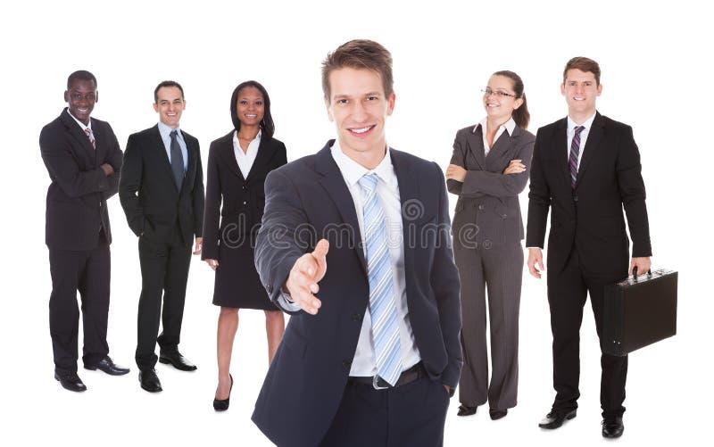 Poignée de main de offre d'homme d'affaires avec l'équipe à l'arrière-plan image libre de droits