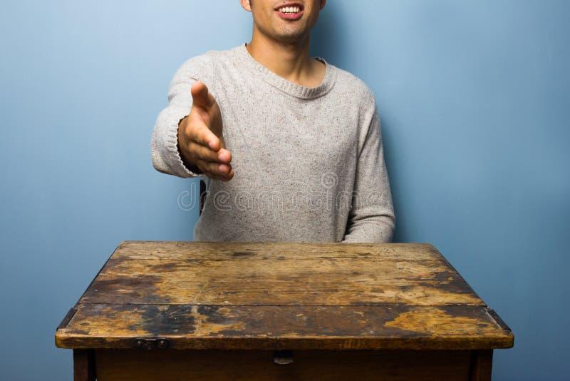 Poignée de main de offre de jeune homme photographie stock libre de droits