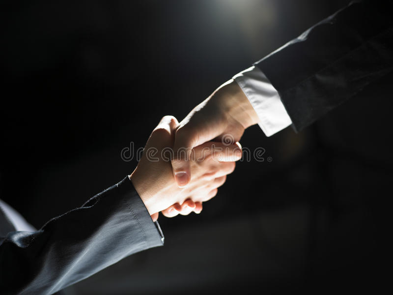 Poignée de main de prise de contact sur léger et l'obscurité photo libre de droits