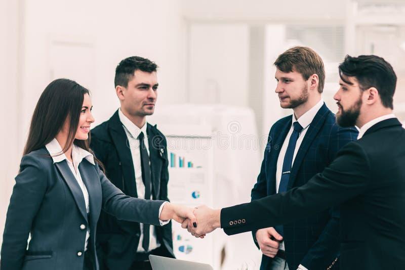 Poignée de main des associés après la signature du contrat dans le lieu de travail dans un bureau moderne photographie stock