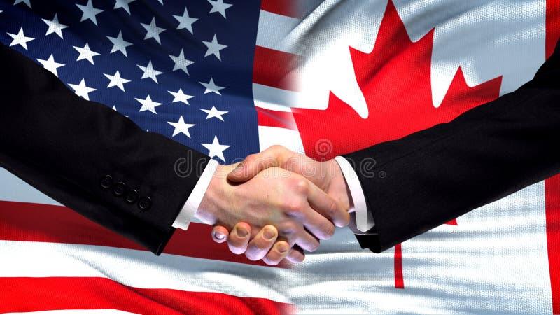 Poignée de main des Etats-Unis et du Canada, amitié internationale, fond de drapeau photographie stock