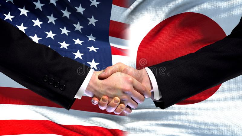 Poignée de main des Etats-Unis et du Japon, amitié internationale, fond de drapeau photo stock